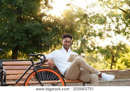 Image of concentrated young african man early morning with bicycle sitting outdoors. Looking aside reading newspaper.