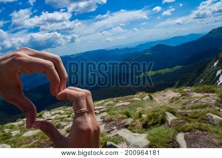 Hands with heart sign on  mountains background. Love concept. Heart shape. Mountain tourism. Symbol of love. Manifestation of love. Expression of feelings. Enjoy. Love and feelings