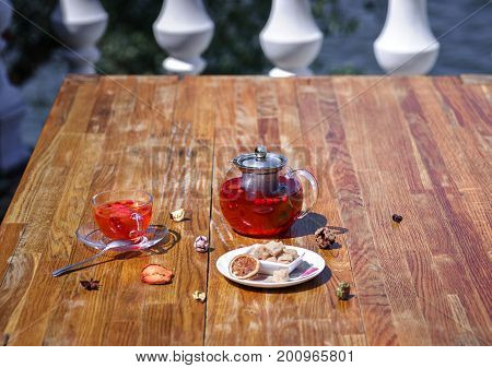 Close-up picture of a teapot full of organic berry beverage on a brown wooden table background. A plate with brown cubes of sugar, kettle and a cup of fresh wild strawberry tea on the table.