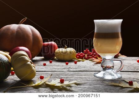 Pumpkin spice latte background. Glass coffee cup with creamy foam, autumn dried leaves, apples and small pumpkins at rustic wood. Fall hot drinks, seasonal offer concept