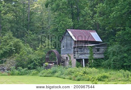 a dilapidated gristmill next to deep woods