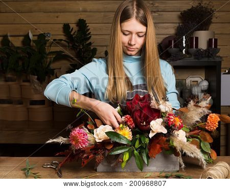 Master class of female florist at work with bunch of flowers. Girl making bouquet of various autumn flowers. Portrait of business woman florist at flower shop