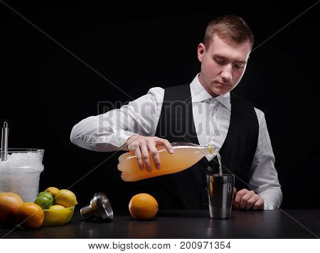 Portrait of an attractive barkeeper in holding a bottle of sweet orange juice on the black background. Alcohol, citruses and a bucket of ice for a shake or smoothie preparation. Copy space,