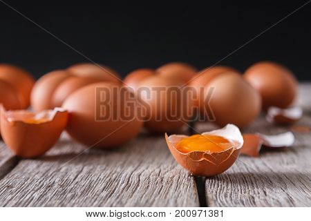 Fresh chicken eggs on wood at black background. Brown eggs with cracked eggshell and yellow yolk on rustic table, copy space. Rural still life, natural healthy food concept, selective focus