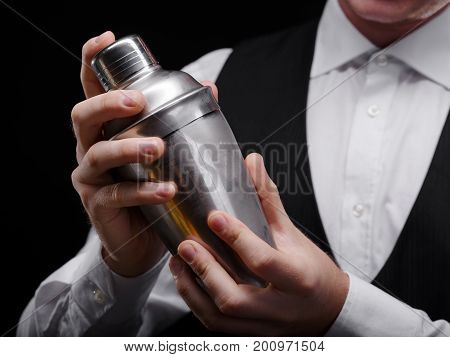 Close-up of a shaker in the hands of a nightclub barkeeper. A pub bartender in a white shirt and black jacket, holding a shaker container for alcoholic drinks on the black background.
