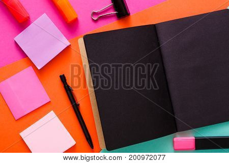 Stationery at modern creative work space. Stylish open notepad with black pages, paperclip, markers and memo notes on abstract multicolored background, top view, copy space