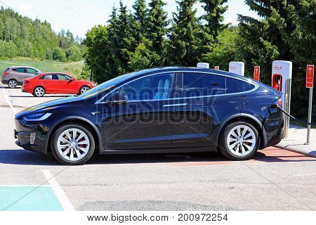 PAIMIO FINLAND - JULY 14 2017: The new Tesla Model X electric car is being charged at Tesla Supercharger. The Model X is an electric luxury crossover SUV manufactured by Tesla Inc.