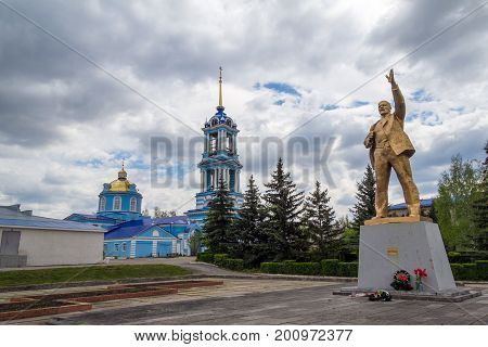 ZADONSK, RUSSIA - JUNE 21, 2016: Golden colored Lenin statue on background of Church of the Assumption of the Blessed Virgin Mary