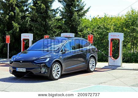 PAIMIO FINLAND - JULY 14 2017: Tesla Model X electric crossover SUV charges battery at Tesla Supercharger station in Paimio. The Model X has an official EPA rated 381-475 km range.