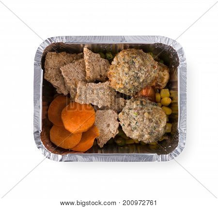 Healthy lunch in foil container. Healthy food take away and delivery. Rusks, cutlets, corn, carrot, green pea in box on white background, closeup, isolated