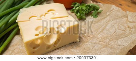 mouthwatering delicious piece of maasdam cheese and a slice on a wooden table surrounded by greenery and tomatoes, border design panoramic banner