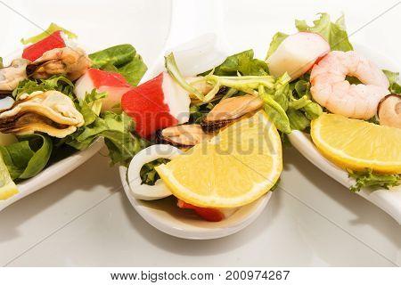 seafood salad and lemon on three porcelain spoon