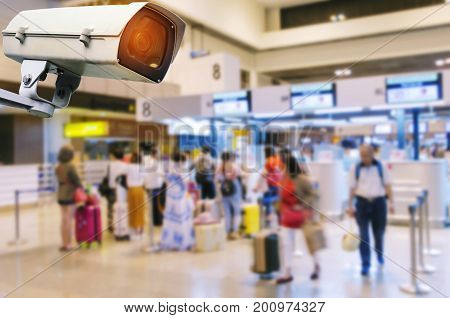 CCTV security camera system operating record and property protection with blurred image of people waiting check in counter at airport surveillance security technology and transportation concept