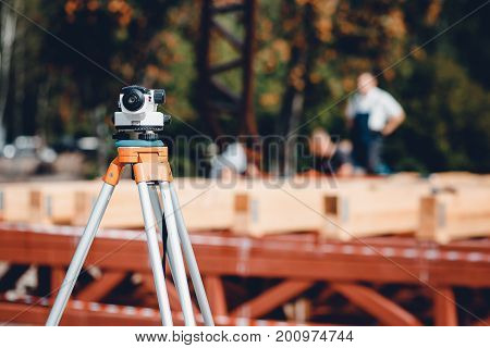Surveyor equipment tacheometer or theodolite outdoors at construction area, builders work in background. concept of construction, designers, instruments.
