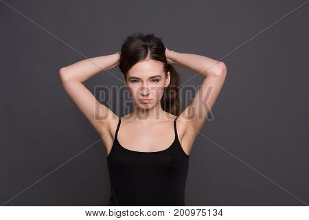 Angry woman with hands on her hair looking at camera. Portrait of grumpy girl, dark background