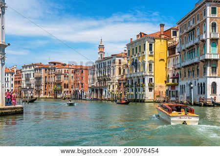 Venice, Italy - May 18, 2017: Water taxis and gondolas are sailing along the Grand Canal. Grand Canal is one of the major water-traffic corridors in Venice.