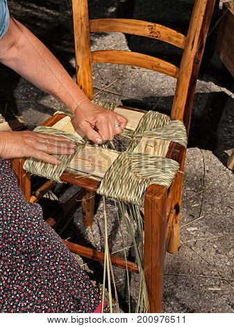 Italian traditional handicraft: woman making a straw seat for wooden chair