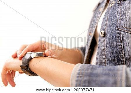 Technology time fast life. Woman in denim jacket looking at her wrist watch