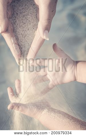 Mother and small baby play with sand slipping through woman hand fingers. Instagram stylization.