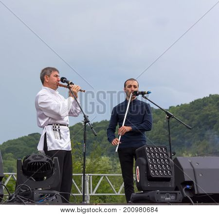 Adygea Russia - August 19 2017: the mans on the stage plays the Adyghe traditional musical instrument Kamyl and panpipe at the open Adyghe cheese festival in Adygea