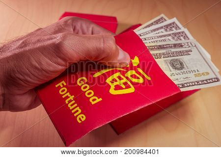 The red envelope or hong bao is used for giving money during the Spring Festival, or Chinese New Year in China and Taiwan. Envelope with the chinese words meaning Good fortune on it, and dollar bills.