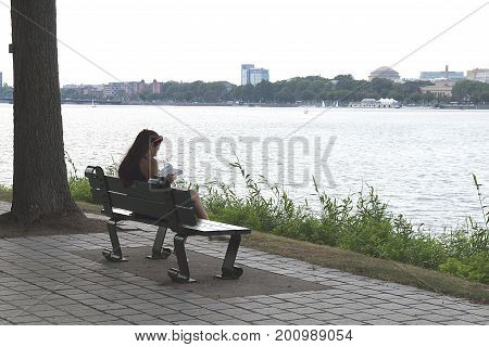 Boston, Massachusetts - August 16, 2017. Girl reading a book in the park on the bench near Charles River in Boston,  Massachusetts