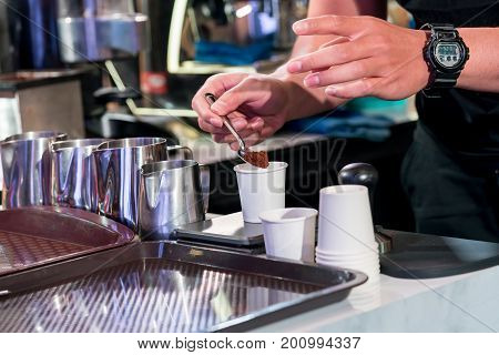 Barista Checking Fine Ground Coffee To Optimize The Grinder