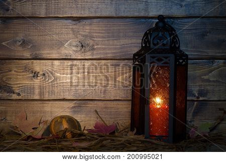 Glowing orange lantern on wood background with copy space