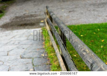 wooden park handle rail close up with concrete path