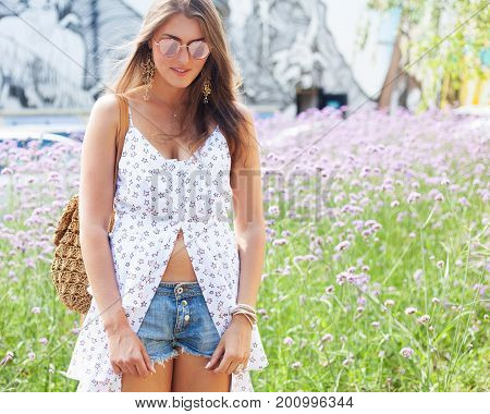 Incredible portrait of a girl in a light white dress, denim shorts and suglasses posing on a hot afternoon in the pearly flowers in the city. Outdoor.