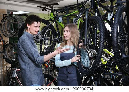 Young man and pretty woman checking bicycle in repair shop
