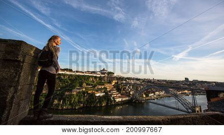 Young woman on the top observation deck on Douro river, overlooking the bridge Dom Luis I, Porto, Portugal.