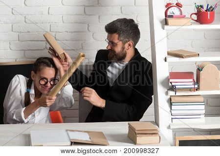 Girl with glasses and bearded man sit at desk and fight with scrolls. Father and schoolgirl on classroom background. Home schooling and back to school concept. Teenager and dad with happy faces