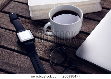 Close-up of black coffee with organizer, laptop, spectacles and smart watch on wooden table