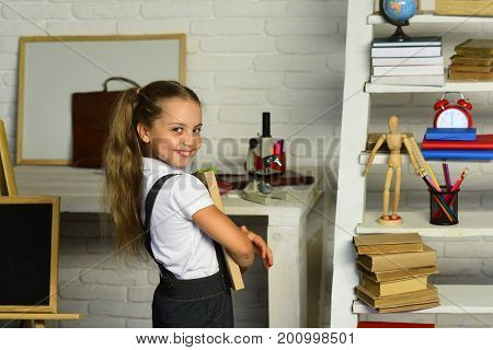 Girl With Cheerful Face Expression Near Desk With School Supplies