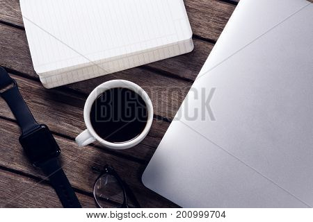 Close-up of black coffee with organizer, laptop, spectacles and smartwatch on wooden table