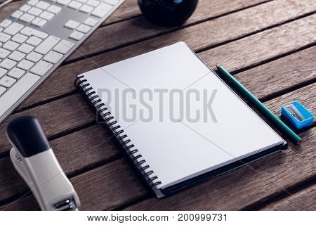 Close-up of keyboard, diary, stationery and stapler on wooden table