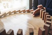 Close up of businessman hand Stopping Falling wooden Dominoes effect from continuous toppled or risk strategy and successful intervention concept for business. poster