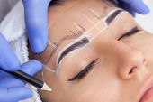 Permanent make-up for eyebrows of beautiful woman with thick brows in beauty salon. Closeup beautician doing tattooing eyebrow. poster