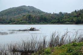 A fisherman works in his boat-house over Samorthong reservoir UthaiThani Thailand