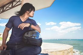 An Asian man sitting under roof next to the sea with his helmet while looking to the sea