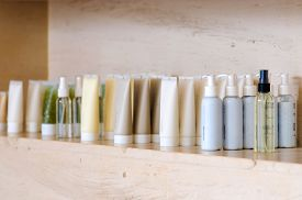 Group of variable skin care container products from natural ingredients on marble shelf