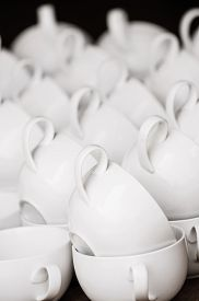 Arranged white coffee cups in pattern ready for morning coffee