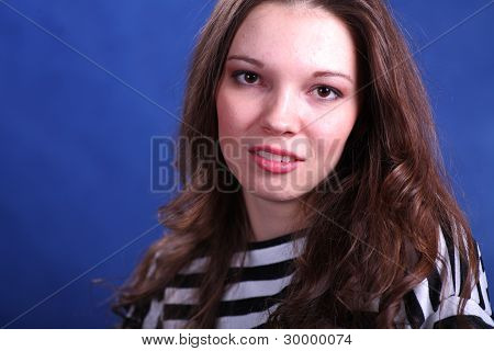Young brunette lady posing on blue background
