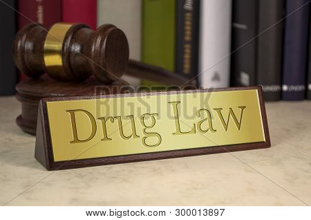 Golden Sign Showing Drug Law With Gavel And Law Book