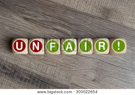 Cubes And Dice With Fair And Unfair On Wooden Background