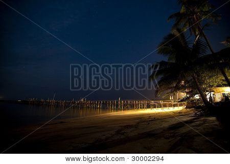 Wooden pier over tropical beach with palm trees