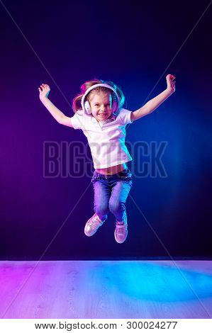 Girl Of 7 Years Old Listening To Music In Headphones And Jump On Dark Colorful Background . Dancing