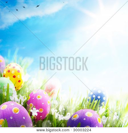 Art Easter Eggs Decorated With Flowers In The Grass On Blue Sky Background