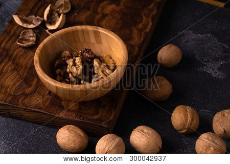 Walnut kernels in wooden bowl and whole walnuts on blue slate surface. Healthy nuts and seeds composition.